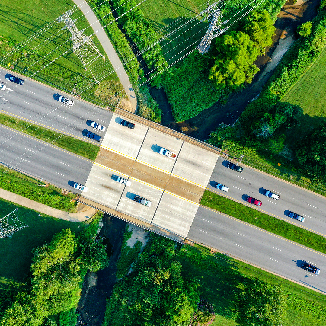 An aerial view of a bridge over the creek and powerlines with cars on the road